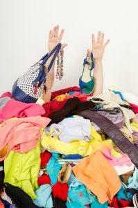 Man buried under an untidy cluttered woman wardrobe. Man reaching for help from to much woman shopping.